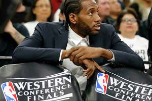The Spurs' Kawhi Leonard fidgets on the bench as his team loses to the Warriors in Game 3 of the Western Conference finals. Leonard has an ankle injury.