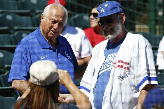 Former Los Angeles Dodgers manager Tommy Lasorda, left, poses for a photo with a fan prior to a spring training baseball game against the Los Angeles Angels, Wednesday, March 9, 2016, in Tempe, Ariz.  (AP Photo/Matt York)