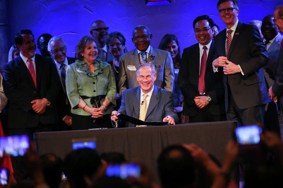 "Gov. Greg Abbott, accompanied by Lt. Gov. Dan Patrick and dozens of pastors including the ""Houston Five"" whose sermons were subpoenaed by the city of Houston, ceremonially signs Senate Bill 24 during the service on Sunday, May 21, 2017, at Woodlands Grace Church in The Woodlands. Texas Senate Bill 24 blocks religious sermons from being subpoenaed by governmental entities. Photo: Michael Minasi, Staff / © 2017 Houston Chronicle"