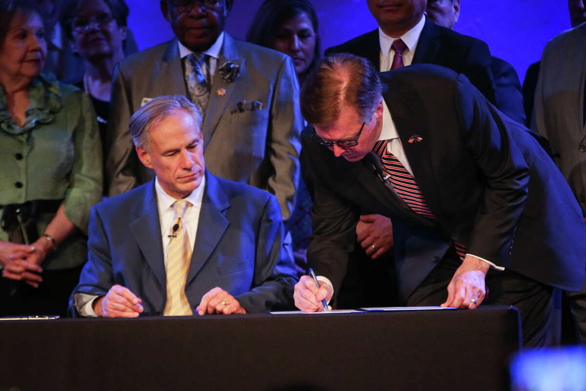 Gov. Greg Abbott looks on as Lt. Gov. Dan Patrick ceremonially signs Senate Bill 24 during the service on Sunday, May 21, 2017, at Woodlands Grace Church in The Woodlands. Texas Senate Bill 24 blocks religious sermons from being subpoenaed by governmental entities.