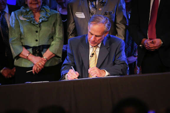 Gov. Greg Abbott ceremonially signs Senate Bill 24 during the service on Sunday, May 21, 2017, at Woodlands Grace Church in The Woodlands. Texas Senate Bill 24 blocks religious sermons from being subpoenaed by governmental entities.