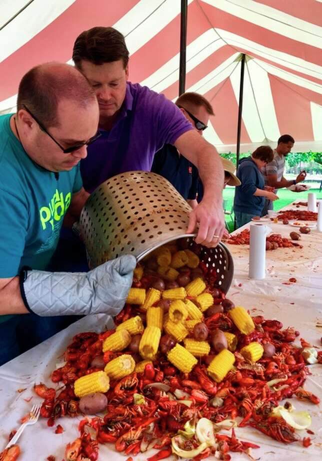 Cooks Lenin Brenes, left, and John Smith pour food onto a table during the 5th annual crawfish boil on Saturday at Memorial Presbyterian Church.