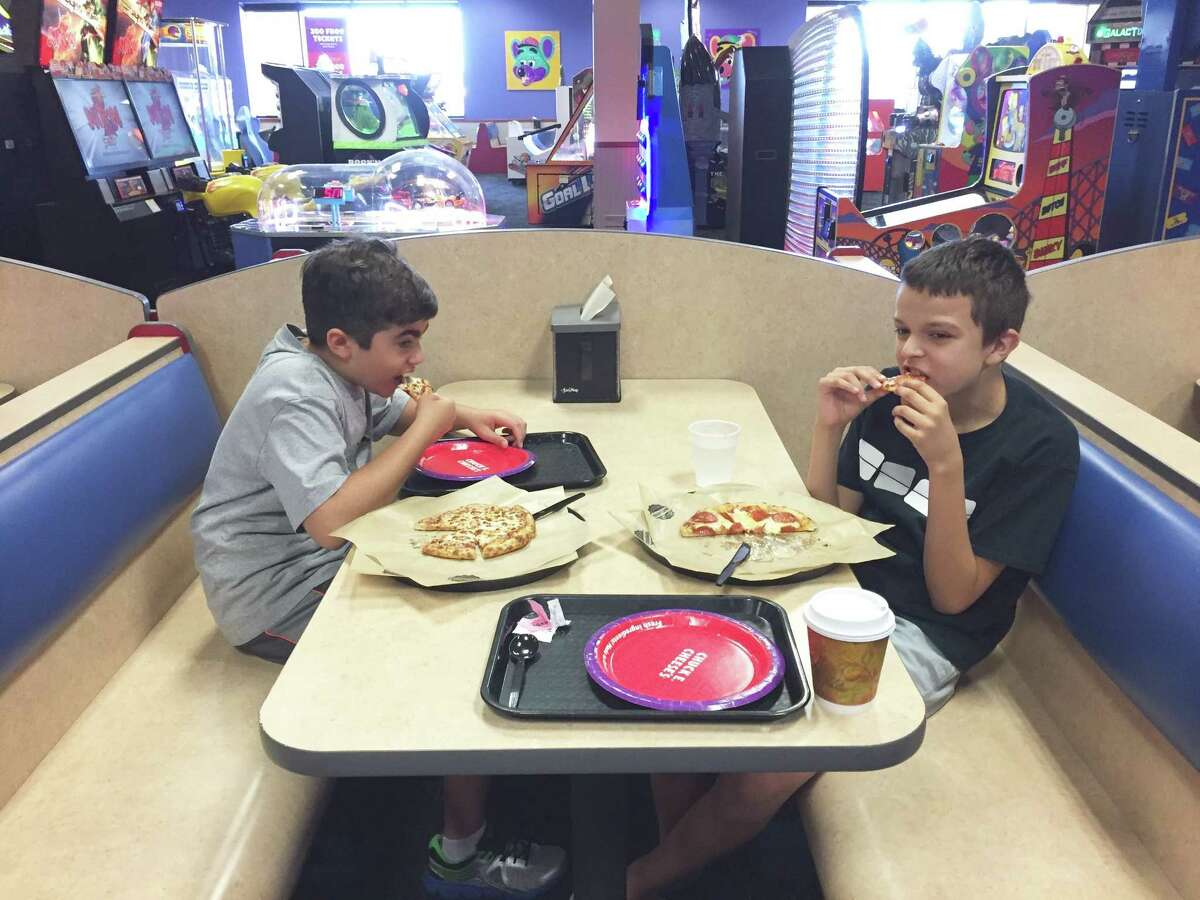 Danny, left, and Paul, both of west Houston, eat pizza at Chuck E. Cheese's on a Sensory Sensitive Sunday.