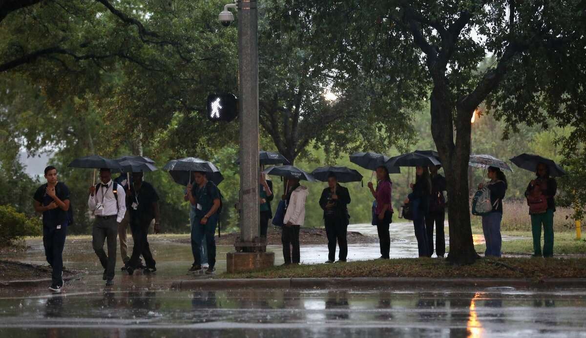 Pedestrians wait to cross the street as rain falls near the Texas Medical Center in Houston on May 22, 2017.