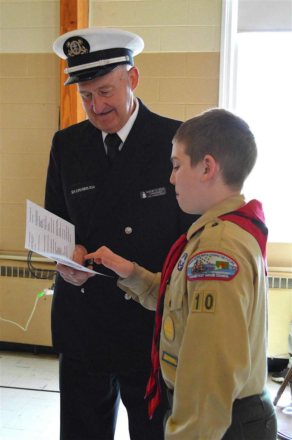 Scout Patrick Clancey, 11, of Fairfield, discusses the program with Commodore Robert Kral of the New England Floatilla at the BSA Troop 10 Eagle Court of Honor, Saturday, May 20, 2017, at First Presbyterian Church in Fairfield, Conn.