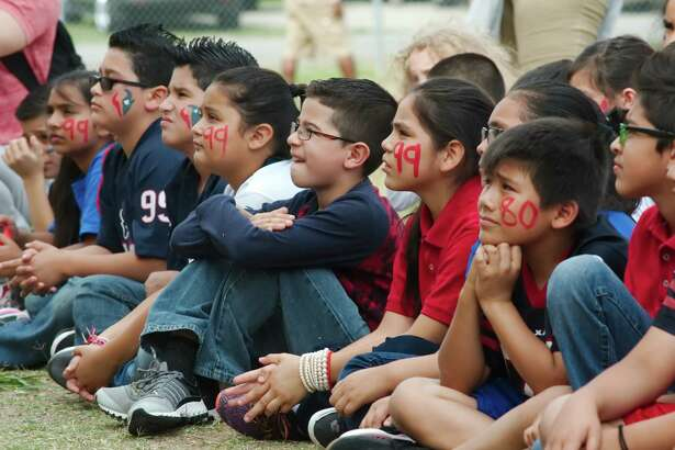 South Houston Elementary School students Paul Galvan, Steven Galvan, Danette Gomez, Eduardo Gutierrez, Magaly Mercado, Melanie Montalvo and Abby Perez listen as Former Houston Texans players and current Houston Texans cheerleaders talk about the importance of a good diet and exercise during a Houston Texans mini-camp at the school Wednesday, May 17.