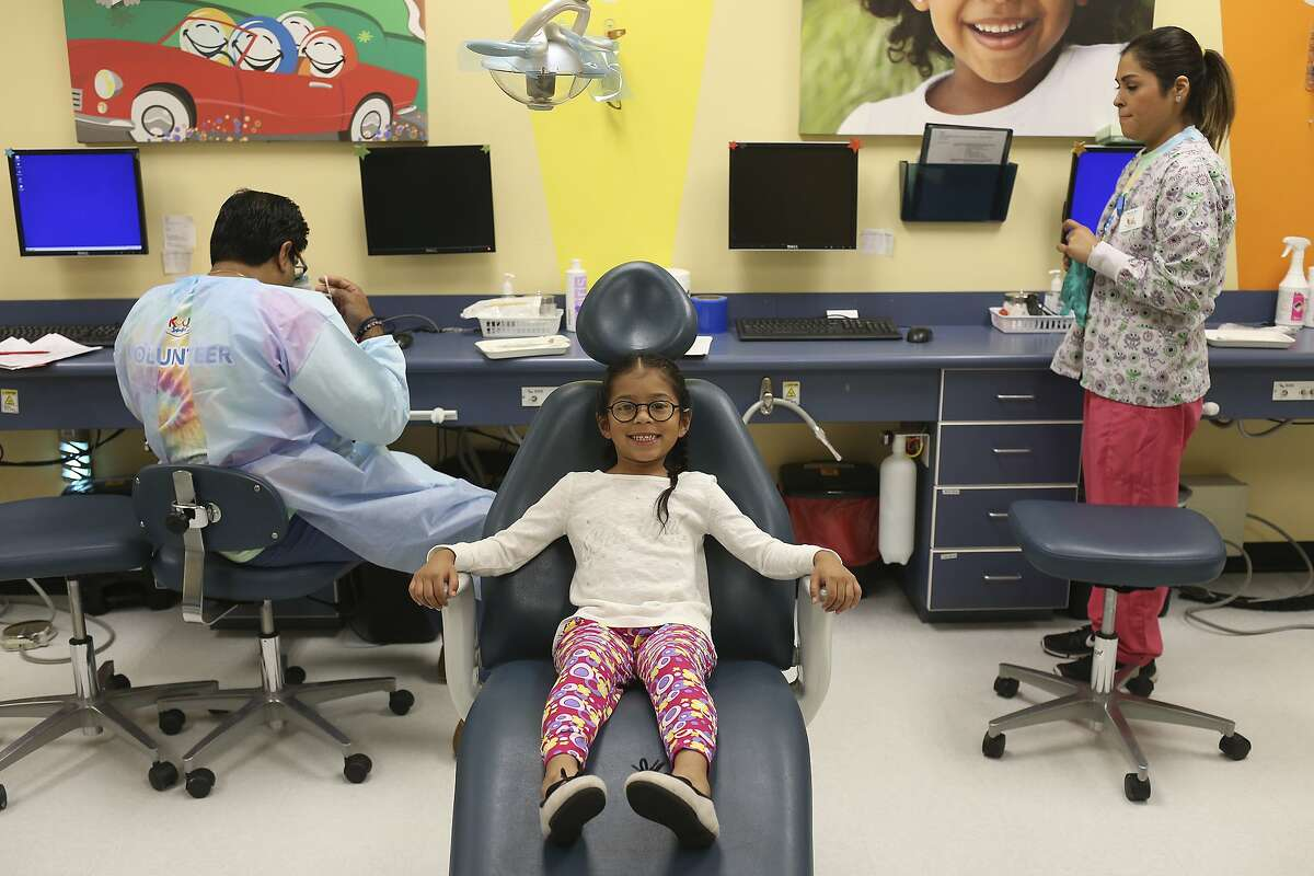 Makayla De Leon, 5, waits for Dr. Kunal Karan, left, during a free dental clinic at Kool Smiles General Dentistry for Kids, Sunday, May 21, 2017. The services were provided as part of the annual Sharing Smiles Day, offering uninsured and underinsured kids up to 18 free dental exams, extractions, restorative care and emergency care.