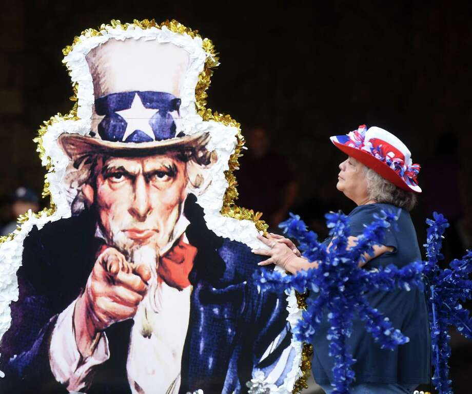 A woman on a float straightens an image of Uncle Sam during the Armed Forces River Parade on the Riverwalk on Saturday, May 20, 2017. Loretta Swit, who played Major Margaret Houlihan on the television show M*A*S*H, was the grand marshal of the event, which featured 26 military-themed floats. Photo: Billy Calzada, Staff / San Antonio Express-News / San Antonio Express-News
