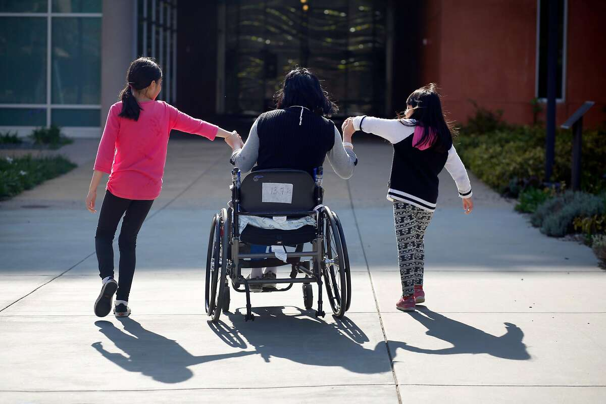 Emma Zhou (center) holds the hands of her daughters as they pull her toward an entrance at Laguna Honda Hospital and Rehabilitation Center after visiting the Virginia Leishman Farm during a visit with their mother during their spring break on Thursday, March 30, 2017 in San Francisco, Calif.