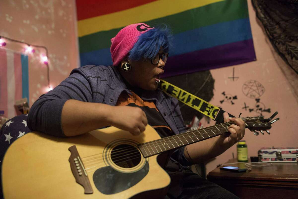 Adam Snow, who is transgender, plays guitar in his bedroom in San Antonio, Texas on February 3, 2017.