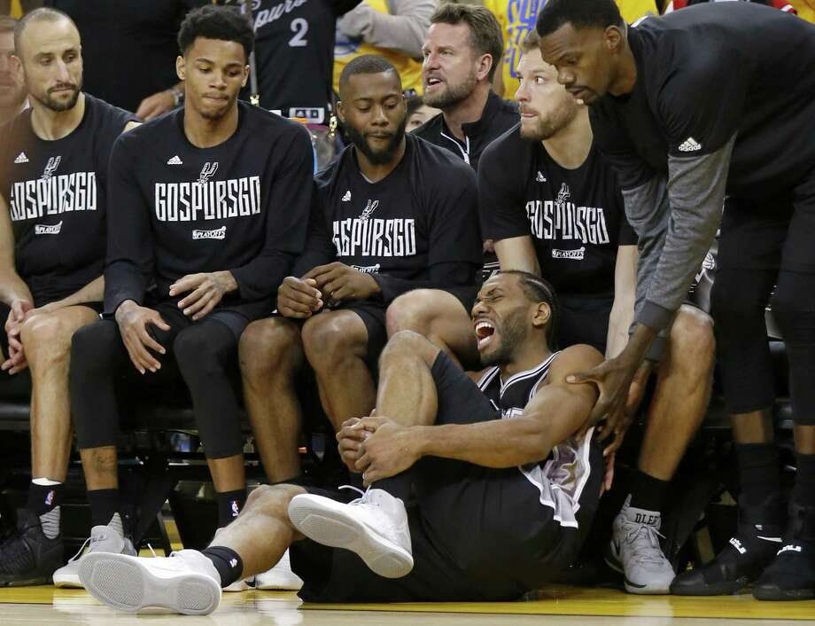 San Antonio Spurs' Kawhi Leonard reacts after being injured on a play as teammates Manu Ginobili (from left), Dejounte Murray, Jonathon Simmons, David Lee, and Dewayne Dedmon look on during second half action of Game 1 in the Western Conference Finals against the Golden State Warriors held Sunday May 14, 2017 at Oracle Arena in Oakland, CA. The Warriors won 113-111. Photo: Edward A. Ornelas, Staff / San Antonio Express-News / © 2017 San Antonio Express-News