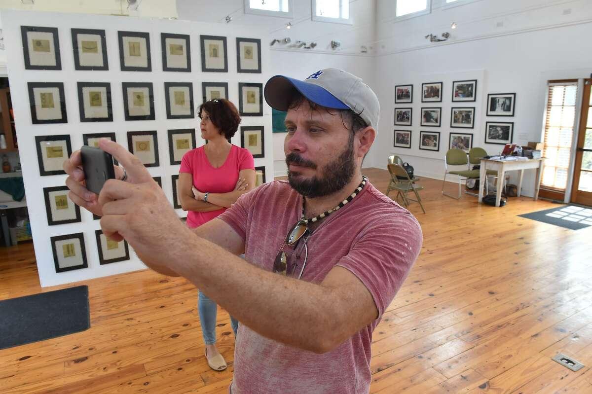 Cuban artist Camilo Villalvilla part of his exhibit at the Bihl Haus Art gallery at 2803 Fredericksburg Rd. Behind him is curator Liam Nodal.