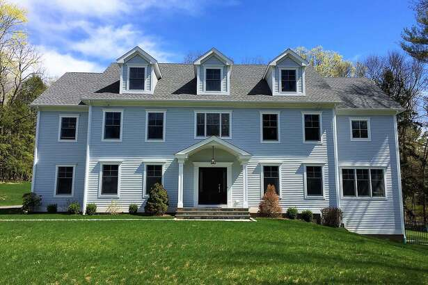 The gray colonial house at 104 Easton Road is energy efficient. It boasts geo-thermal heating, extra insulation, and other utility cost-saving features.