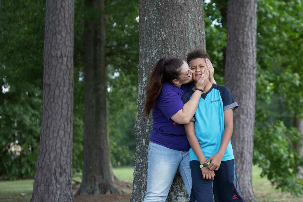 Nicole Rechner kisses her son Demarcus Fuller, 12, at the Tidwell Park, Saturday, May 20, 2017, in Houston. Rechner transferred him to HISD's Hamilton Middle School where he now receives appropriate special education services after years of being denied the services.