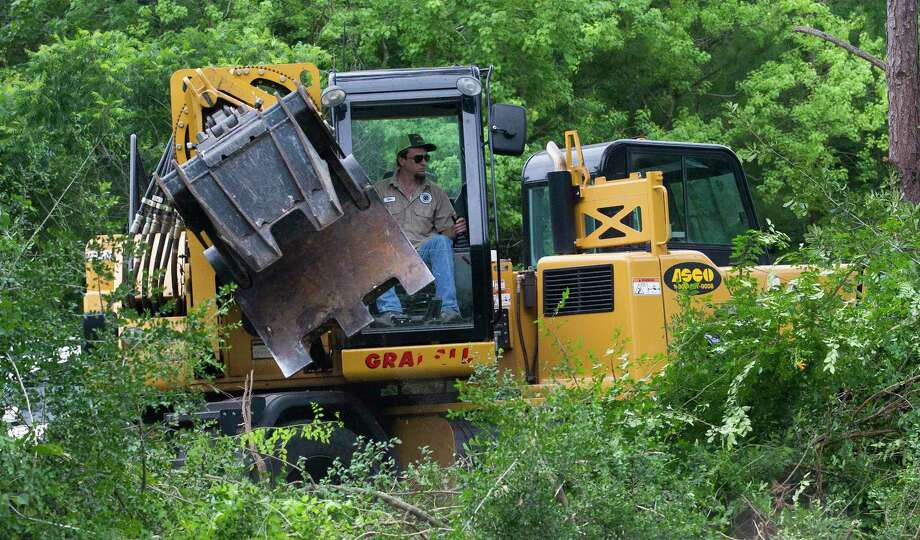 A worker clears trees and shrubs as part of a construction project to create two additional lanes on Research Forest Drive near the intersection of Branch Crossing Drive and Research Forest Drive May 18 in Conroe. Photo: Jason Fochtman, Staff Photographer / © 2017 Houston Chronicle