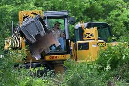 A worker clears trees and shrubs as part of a construction project to create two additional lanes on Research Forest Drive near the intersection of Branch Crossing Drive and Research Forest Drive May 18 in Conroe.