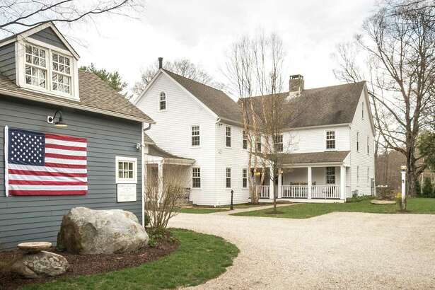 An American flag is displayed on the guest cottage of the updated vintage colonial farmhouse at 3808 Redding Road in Fairfield, a property that has more than 16 acres of land, a barn and other agricultural amenities.