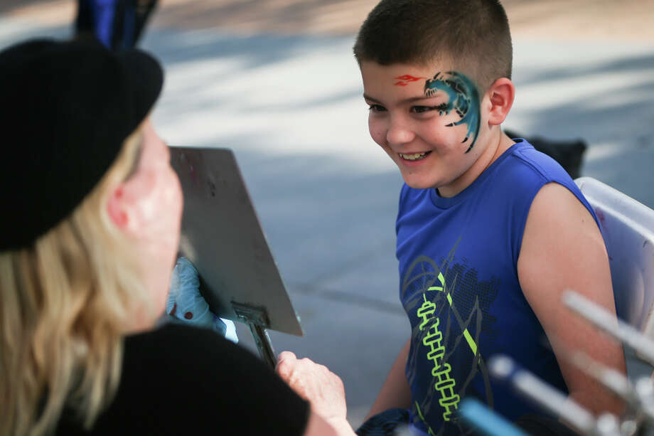 Bradin Smith, of Willis, smiles in the mirror while looking at the fresh dragon design painted on his face by Donna Callaway, of Best Entertainers, during the Memorial Day festivities on Saturday, May 28, 2016, at Town Green Park. Photo: Michael Minasi, Staff / © 2017 Houston Chronicle