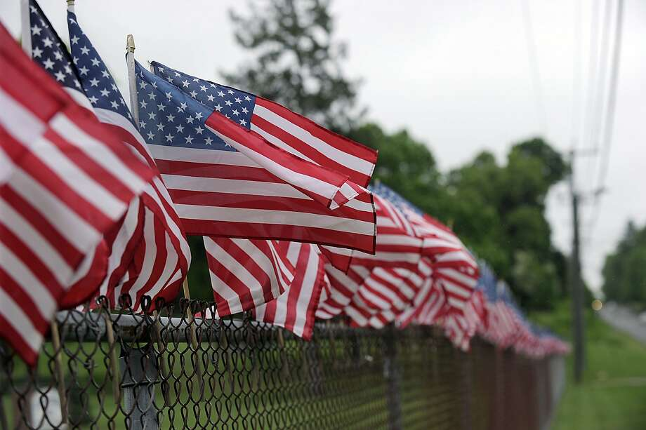 """Children at Huckelbury Hill Elementary in Brookfield, Conn., adorned the fence in the front of their school Monday with hundreds of American flags in honor of Memorial Day. In past years their """"""""field of flags"""""""" was planted in the grass. This year it was decided to use the fence to avoid the possibility of the flags touching the ground — a violation of American flag protocol. Photo: Carol Kaliff, Hearst Connecticut Media"""