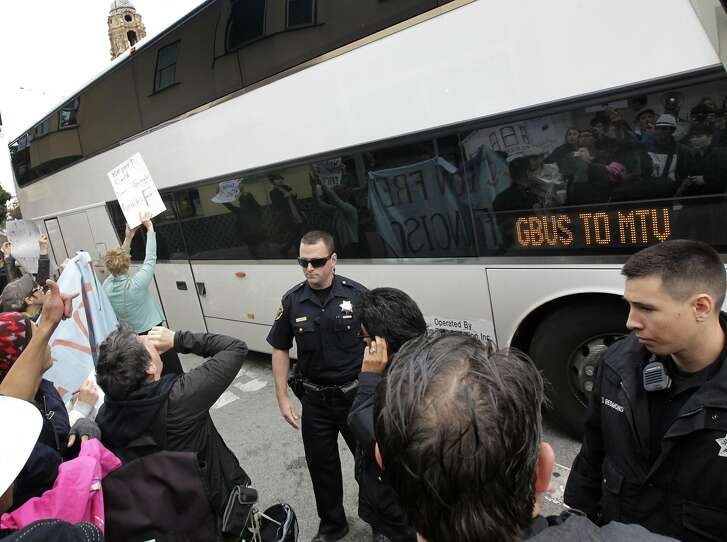Police officers move in to clear protesters away from a Google bus at 18th and Dolores streets in San Francisco, Calif. on Friday, April 11, 2014. The demonstrators are angry with the high number of Ellis Act evictions on tenants.