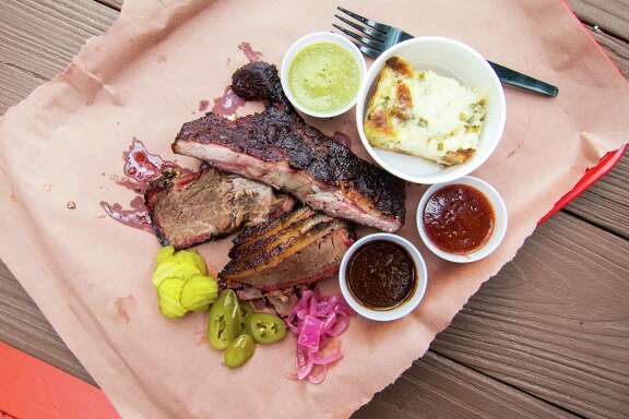 Ribs and brisket with tomato, tomatillo and mole sauces, and corn pudding at Tejas Chocolate in Tomball