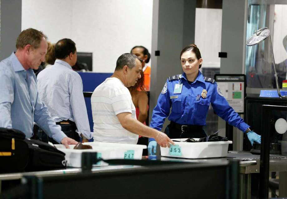 A TSA officer helps travelers put their belongings through an x-ray machine, Tuesday, May 2, 2017, at Miami International Airport in Miami. TSA is rolling out a new CT scanner that may one day allow travelers to pass through security without removing laptops and liquids from their carry-on luggage. (AP Photo/Wilfredo Lee) Photo: Wilfredo Lee, STF / Copyright 2017 The Associated Press. All rights reserved.