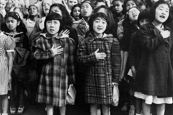 Second generation Japanese Americans Helene Nakamoto Mihara, 7, left, and Mary Ann Yahiro, 7, center, recite the Pledge of Allegiance the Raphael Weill School in San Francisco, California before being sent to the Topaz Internment Camp in Utah in April, 1942. Photograph by Dorothea Lange