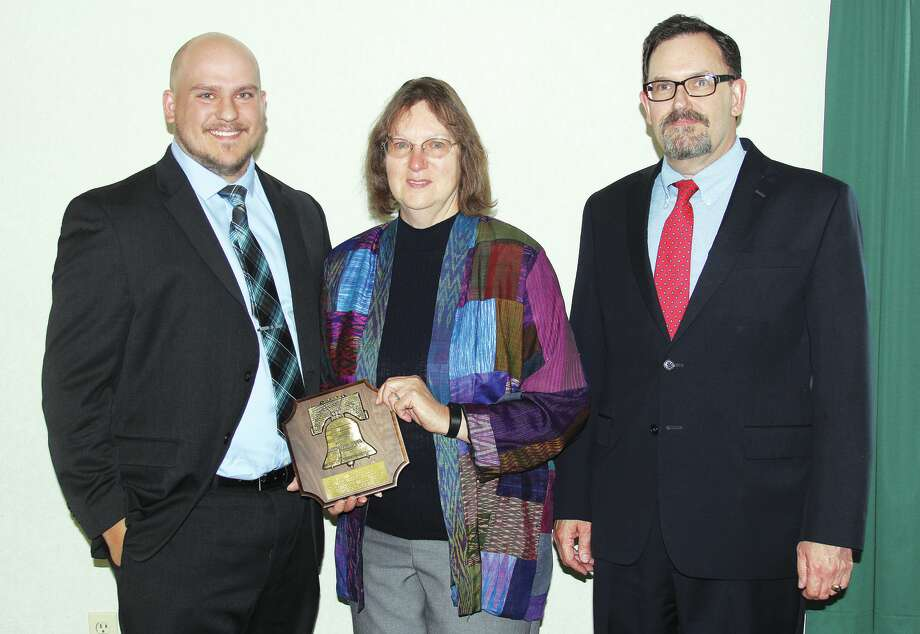 From left, Aaron and Judy Grigg accepted the Liberty Bell Award on behalf of Robert L. Grigg who was this year's recipient. Dallas Rooney, president of the Huron County Bar Association, presented the plaque to the duo recently at a luncheon honoring the late Bad Axe teacher. Photo: Bradley Massman/Huron Daily Tribune