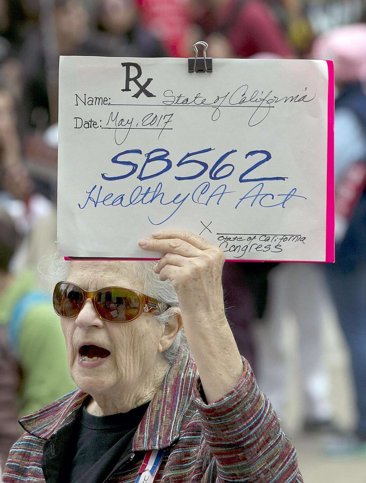 Caroline Elam holds up a mock prescription order calling for passage of SB562, a single-payer health care bill, during a march to the Capitol, Wednesday, April 26, 2017, in Sacramento, Calif. The bill, by Democratic state Sens. Ricardo Lara, of Bell Gardens, and Toni Atkins, of San Diego, would guarantee health coverage with no out-of-pocket cost for all California residents, including people living in the country illegally is to be heard in the Senate Health Committee on Wednesday. (AP Photo/Rich Pedroncelli)