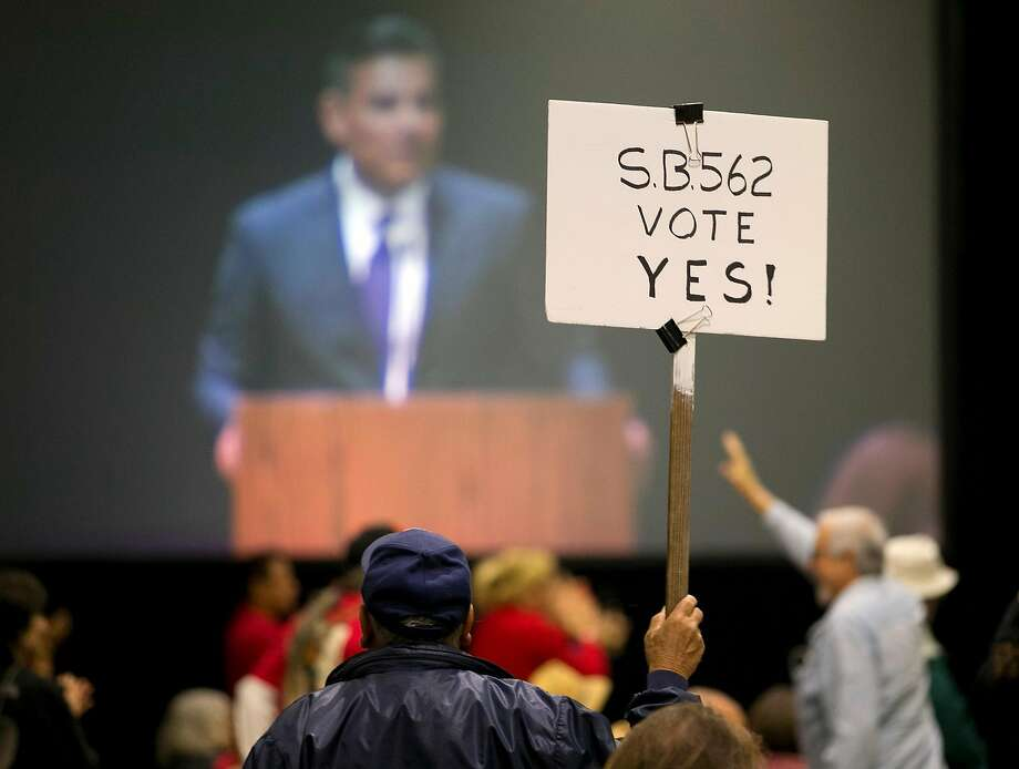 A supporter of SB562, a single-payer health care bill, holds up his sign as one of the bill's co-authors, state Sen. Ricardo Lara, D-Bell Garden, is seen on a large screen at a rally Wednesday, April 26, 2017, in Sacramento, Calif. SB562 by Lara, and Sen. Toni Atkins, D-San Diego, that would guarantee health coverage with no out-of-pocket cost for all California residents, including people living in the country illegally is to be heard in the Senate Health Committee, Wednesday. Photo: Rich Pedroncelli / Associated Press