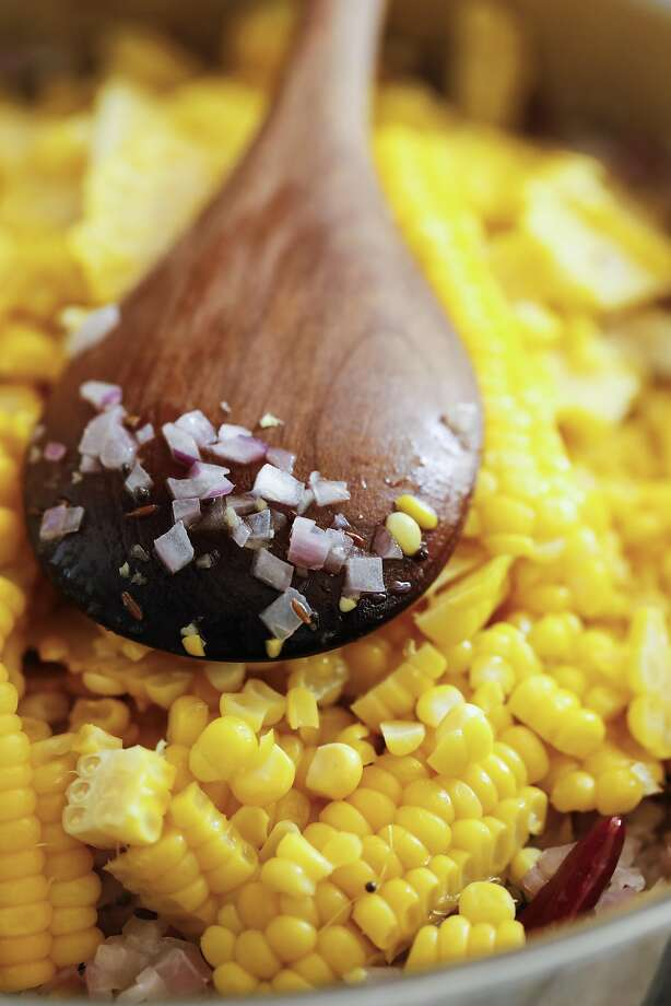 Mixing the fresh corn into the pan. Photo: Russell Yip, The Chronicle