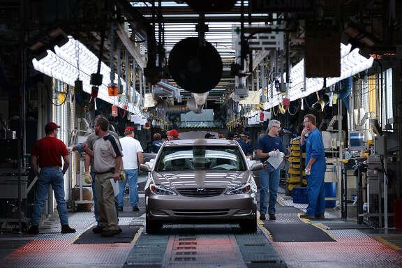 A Toyota Camry is checked for quality in this 2002 photo at the end of the assembly process by quality control inspectors at the Toyota Motor Manufacturing plant in Georgetown, Ky. (File Photo)