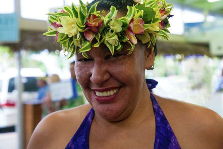 """Lydia Nga, with the Tourism Office, wears the traditional flower """"ei,"""" first cousin to a Hawaiian lei."""