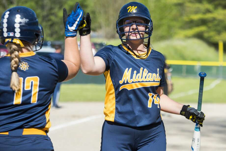 Midland senior Jillian Elmer, left, high-fives sophomore Gillian Schloop during a double-header at H.H Dow High School in Midland on Monday. Photo: Danielle McGrew Tenbusch