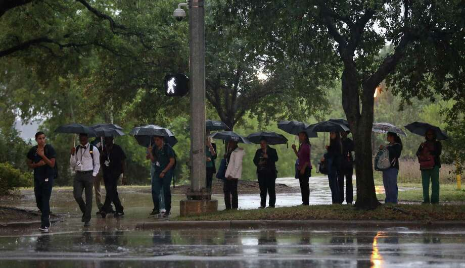 Pedestrians wait to cross the street as rain falls near the Medical Center Monday, May 22, 2017, in Houston. ( Godofredo A. Vasquez / Houston Chronicle ) Photo: Godofredo A. Vasquez, Weather / Godofredo A. Vasquez / Houston Chronicle