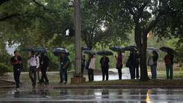 Pedestrians wait to cross the street as rain falls near the Medical Center Monday, May 22, 2017, in Houston. ( Godofredo A. Vasquez / Houston Chronicle )