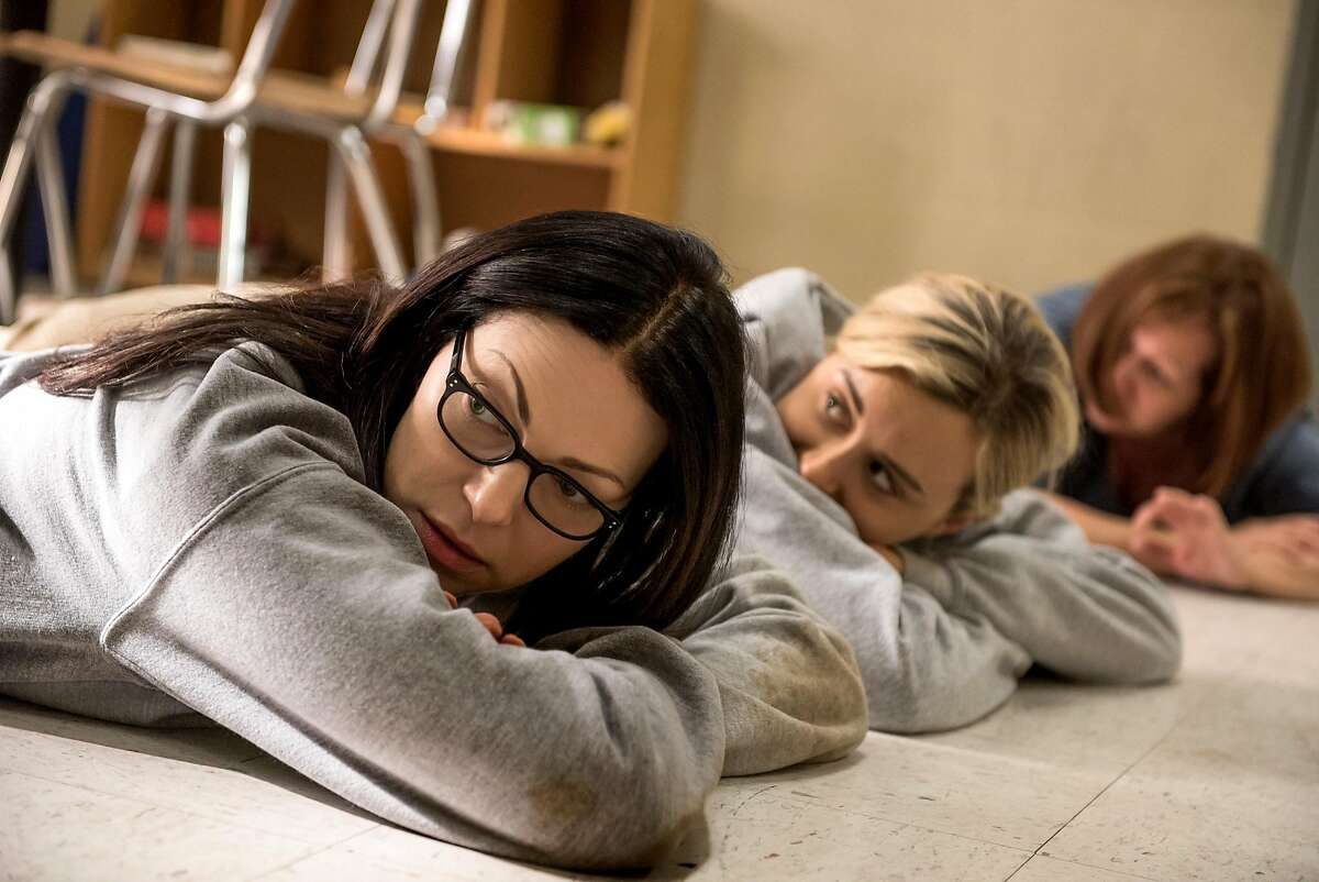 Laura Prepon and Taylor Schilling as Alex and Piper try to steer clear of trouble as their fellow inmates' take guards as hostages and attempt to take control of the prison in Season 5 of 'Orange is the New Black' on Netflix.