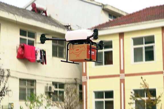 A drone takes off to deliver a  JD.com parcel from a village in China. JD.com says its planned drone delivery network in Shaanxi would cover a 200-mile radius and have drone air bases throughout the province.
