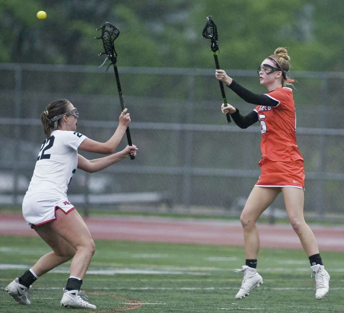 New Canaan High School's Caroline Schuh tries to block the pass of Ridgefield High School's Caeleigh Tannian in the FCIAC girls lacrosse semi-finals played at Norwalk High School. Monday, May 22, 2017