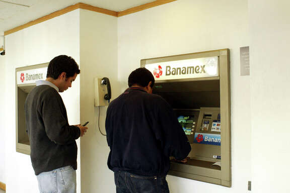 Bank customers use an automated teller machine (ATM) at a Banamex branch bank in Mexico City on Thursday, January 29, 2004. Banamex, Mexico's second-biggest bank and a unit of Citigroup Inc., is among the banks charging into the remittance market with cheaper rates than Western Union and payments via ATM cards. Photorapher: Sarah Martone/Bloomberg News
