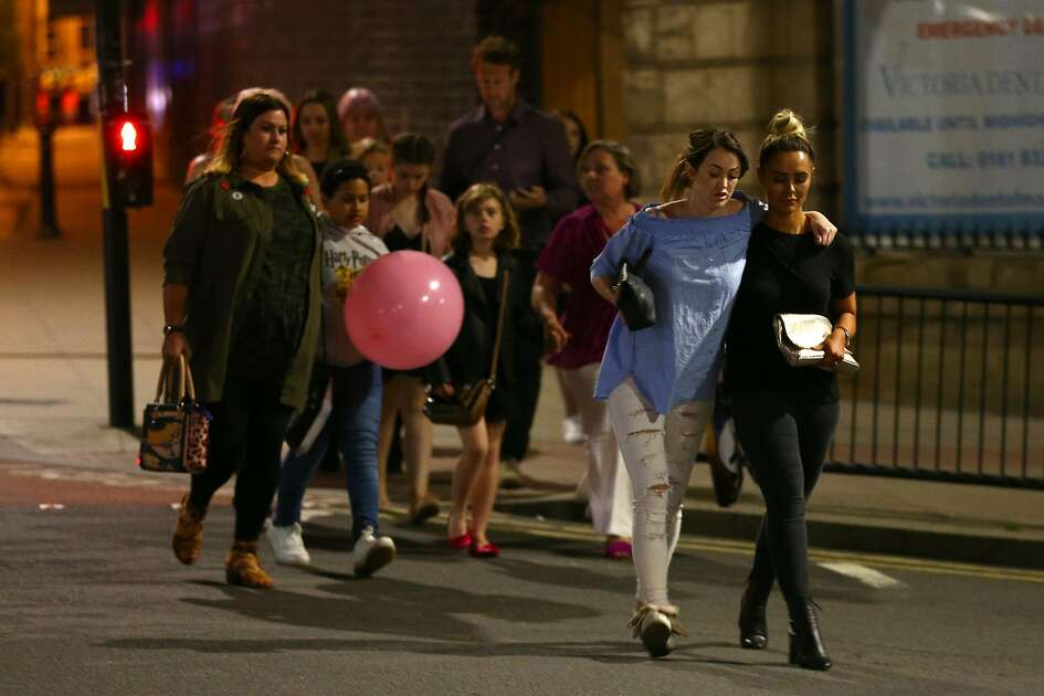 MANCHESTER, ENGLAND - MAY 23: Members of the public are escorted from the Manchester Arena on May 23, 2017 in Manchester, England.  There have been reports of explosions at Manchester Arena where Ariana Grande had performed this evening.  Greater Manchester Police have have confirmed there are fatalities and warned people to stay away from the area. (Photo by Dave Thompson/Getty Images)