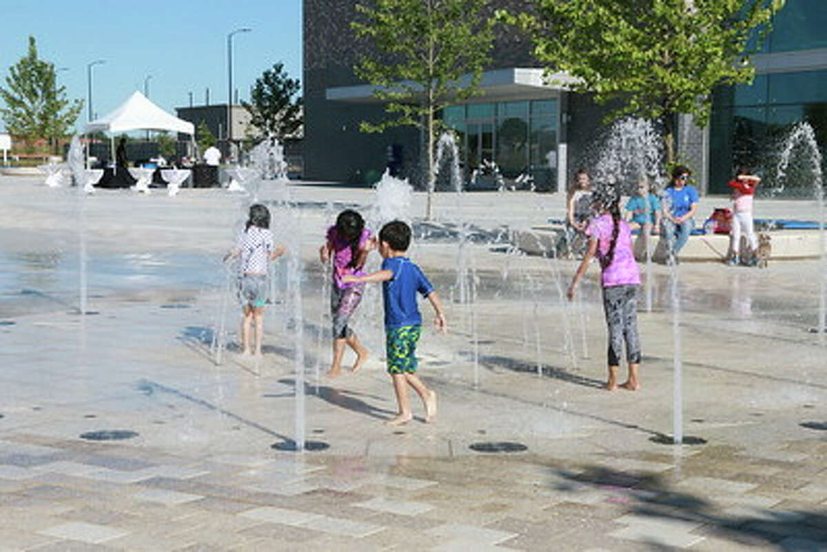Children play in the fountain in the plaza at the Smart Centre in Sugar Land during May 1 grand opening festivities.