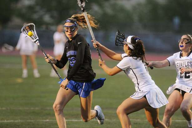From left; Darien's Katie Ramsay attacks the net defended by Staples' Alexa Mysel and Samantha Pacilio in the first half of Darien's 23-4 victory in the FCIAC girls lacrosse semifinals at Norwalk High School on Monday.