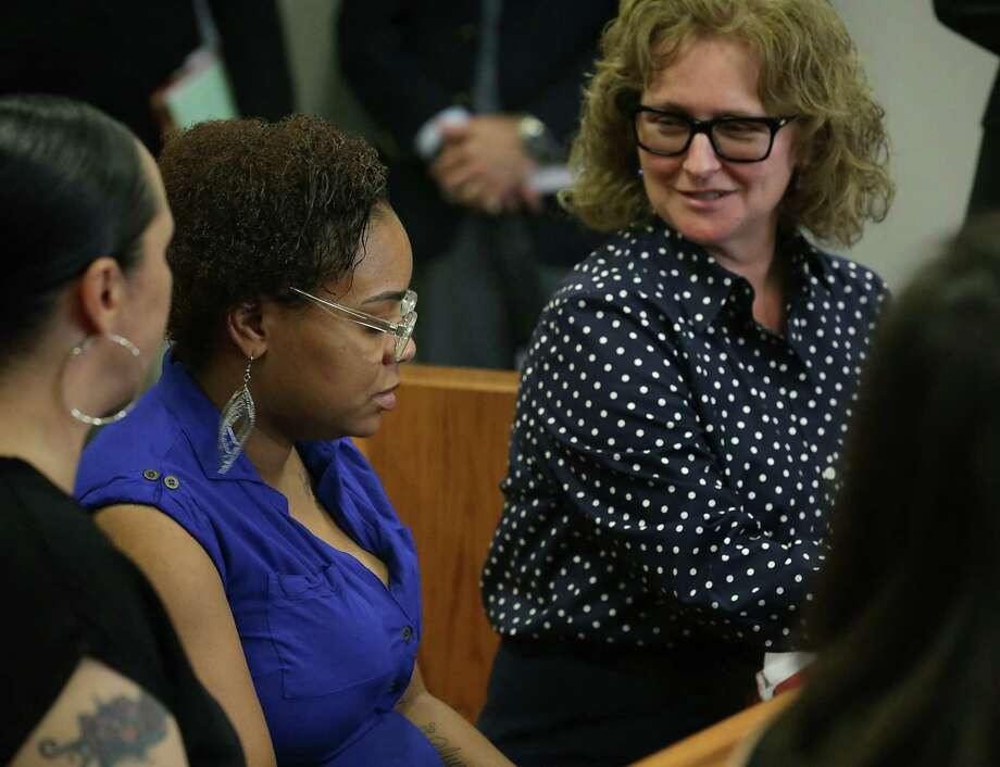 Karn Corby, a lawyer, right, speaks with the mother, center, of the 14-year-old girl who is seen in a video on social media being restrained by several San Antonio police officers. The young woman appeared in juvenile court on May 22, 2017. Photo: Bob Owen /San Antonio Express-News / ©2017 San Antonio Express-News