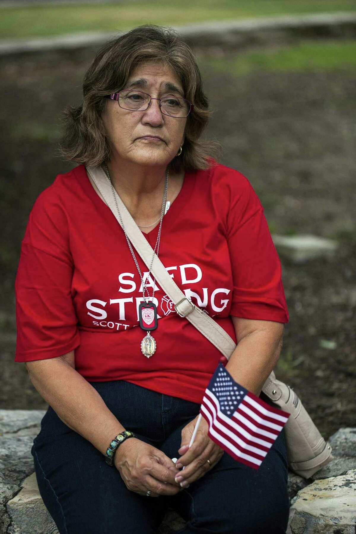 Lillie Gonzales sits in Alamo Plaza before a march and vigil for her nephew, fallen San Antonio firefighter Scott Deem, on May 22, 2017.
