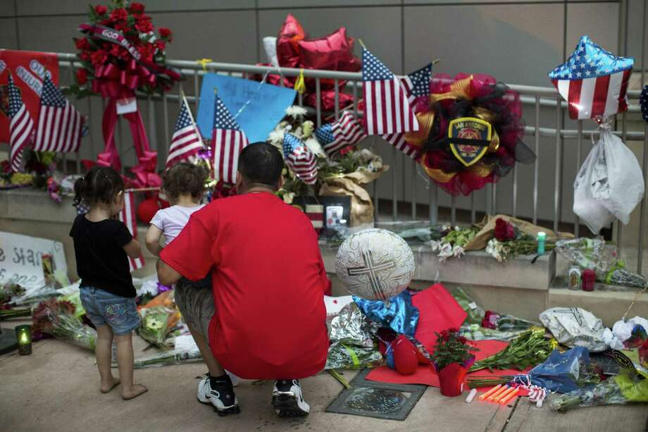 Mourners continue to pay their respects to San Antonio Fire Department firefighter Scott Deem at a memorial outside the Public Safety Building downtown. Photo: Ray Whitehouse /For The San Antonio Express-News
