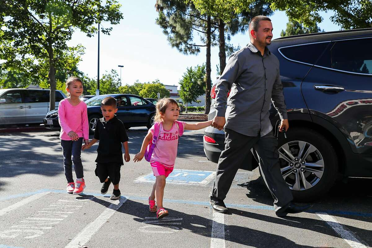 (l-r) Alexia Provencio, 6, Anthony Provencio,4, and Alicia Provencio,3, make their way into Baskin Robbins to get ice cream with their father Michael Provencio in Manteca, California, on Monday, May 22, 2017. Michael fostered Anthony when Anthony was 18-months but has since fully adopted him. Michael was a former foster youth.