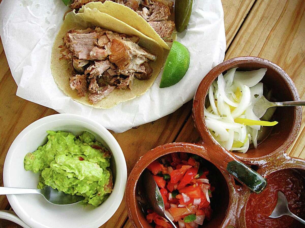 Carnitas tacos, a trio of condiments and guacamole from Carnitas Lonja