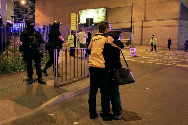 """Armed police stand guard at Manchester Arena after reports of an explosion at the venue during an Ariana Grande gig  in Manchester, England Monday, May 22, 2017. Police says there are """"a number of fatalities"""" after reports of an explosion at an Ariana Grande concert in northern England. (Peter Byrne/PA via AP) ORG XMIT: TKMY802"""