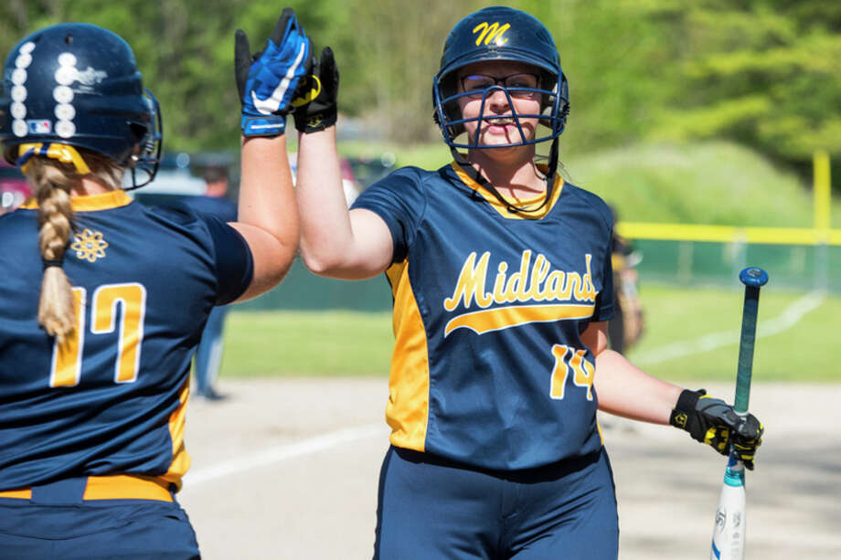 DANIELLE McGREW TENBUSCH | for the Daily News Midland senior Jillian Elmer, left, high-fives sophomore Gillian Schloop during a double-header at H.H Dow High School in Midland on Monday.